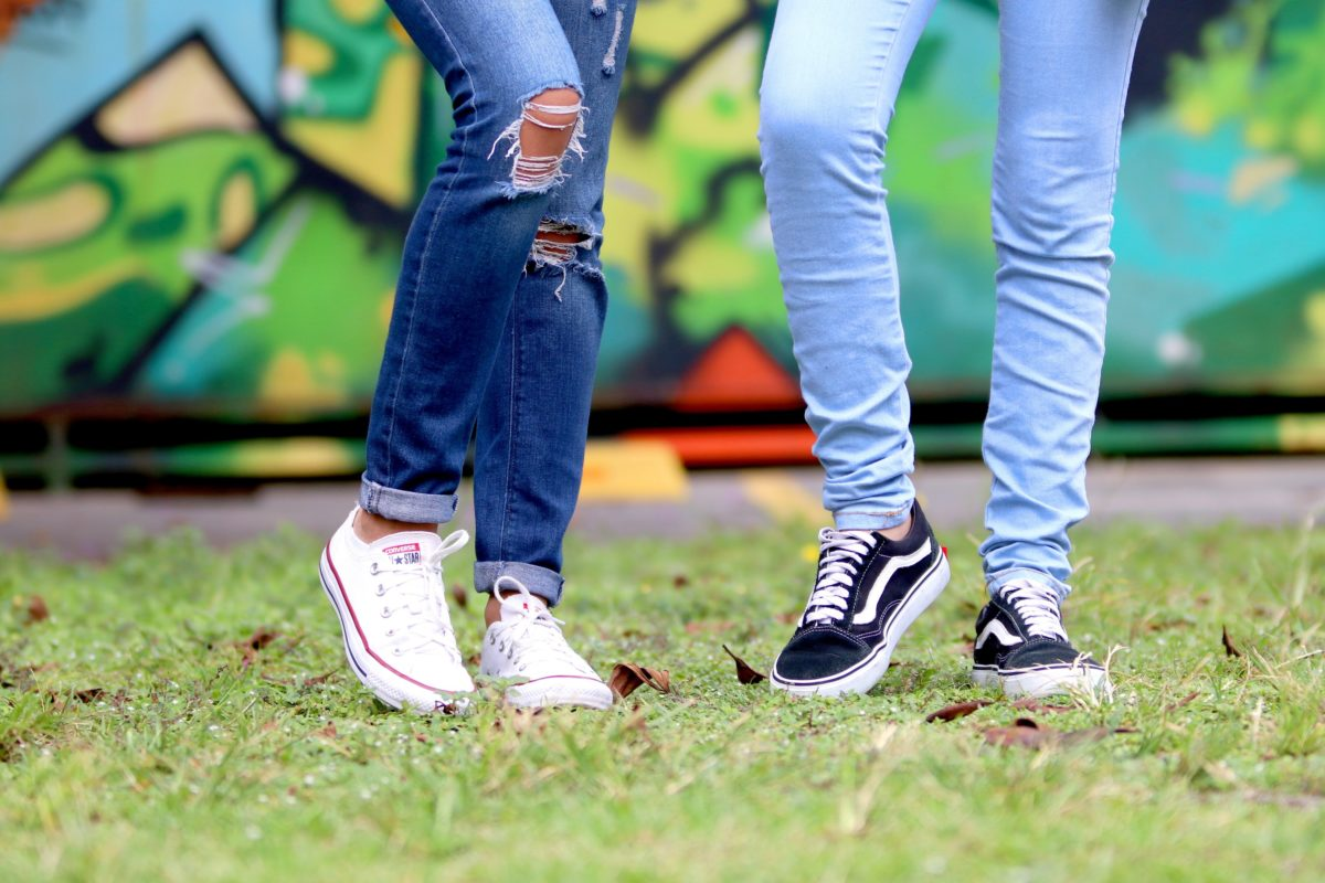 Two young people stand on a lawn.