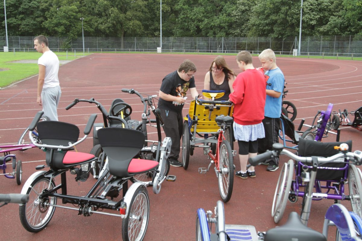 A group of cyclists get ready to ride in tandem on an adaptive bike.