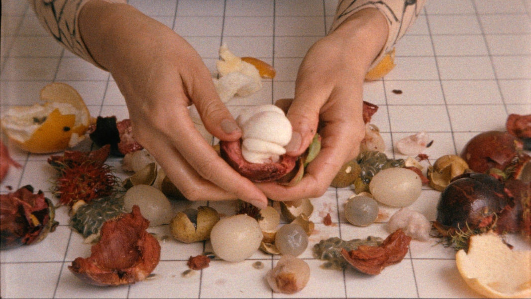 A pair of hands pull apart small items of fruit and vegetables in Sriwhana Spong's short film Castle-Crystal.