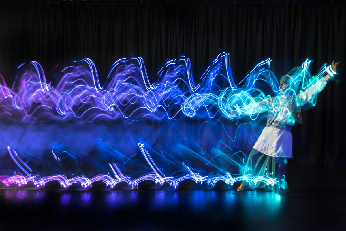 A dancer moves across the stage in a colourful show of lights.