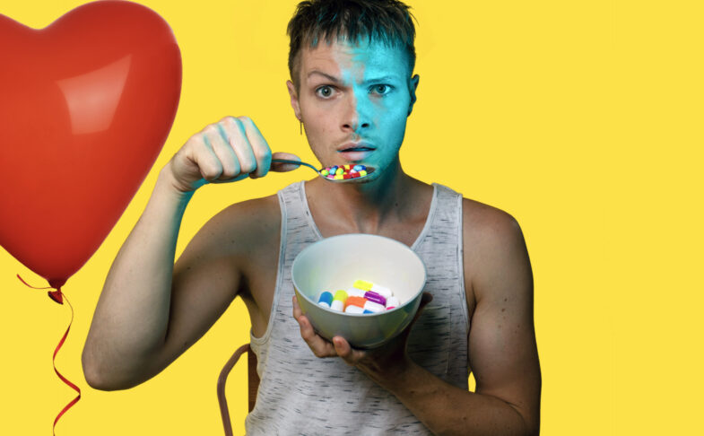 Theatre-maker Nathaniel Hall stands against a bright yellow background holding a bowl of brightly coloured pills. He hold them to his mouth on a spoon as if they are like breakfast cereal.