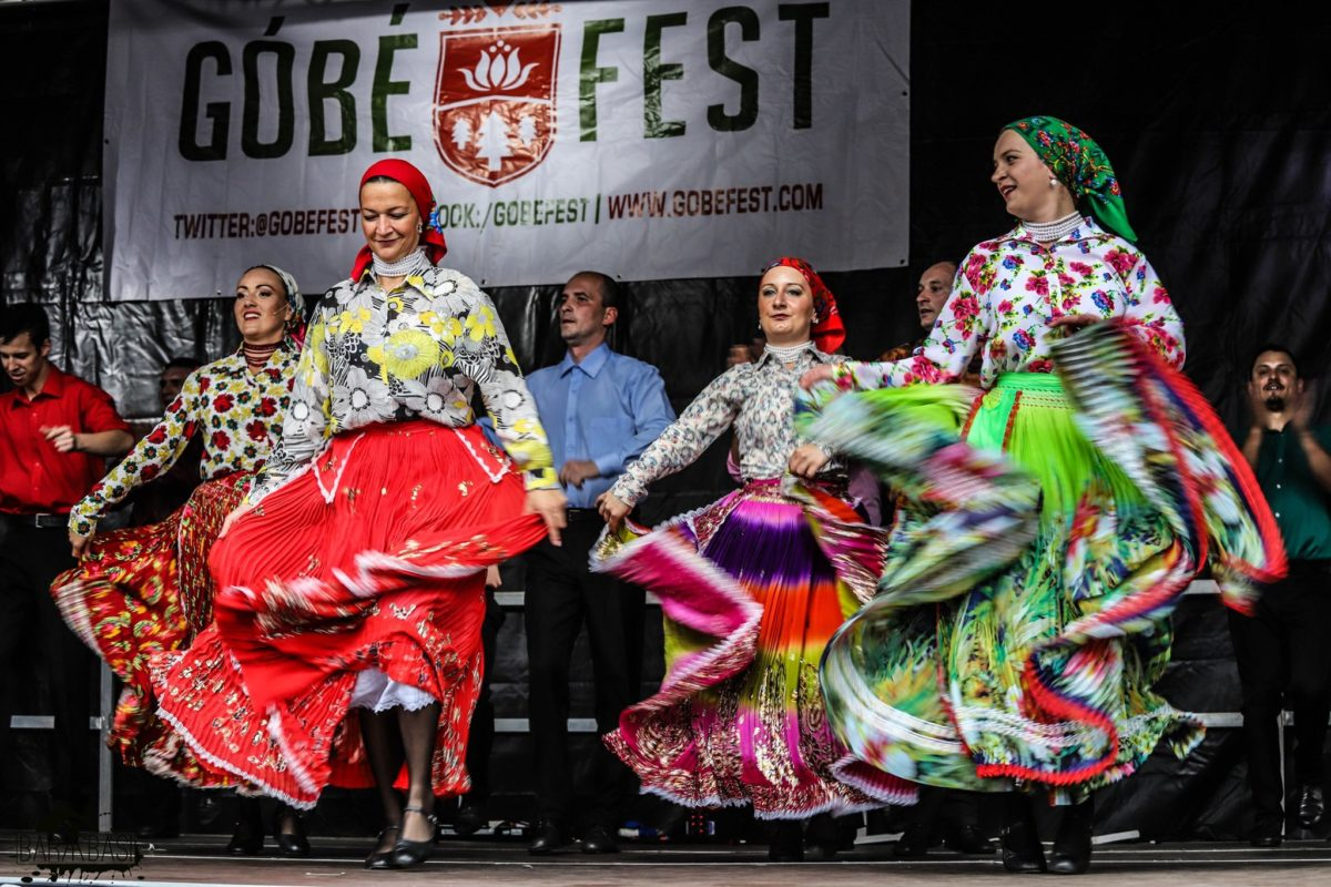 The dancers at Góbéfest wearing bright colourful clothing as they move on stage.