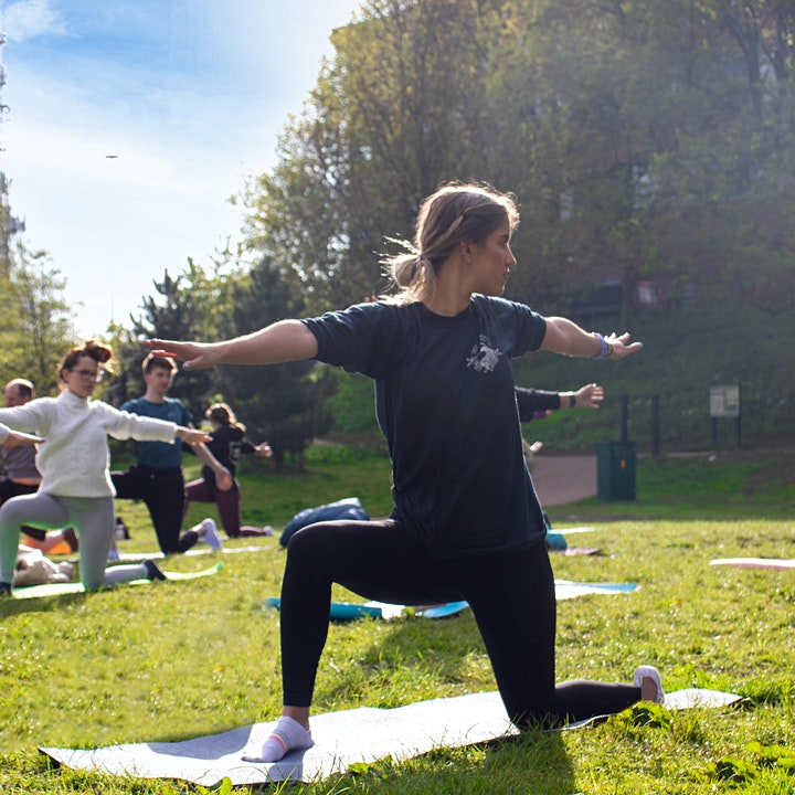 A yoga class takes place outside in a field.
