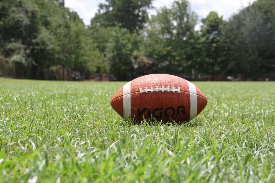 An american football sits on a grassy pitch.