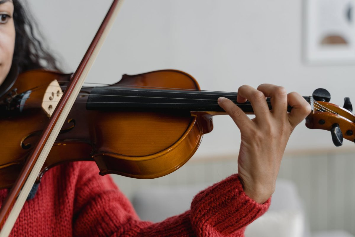 A young person plays a violin.