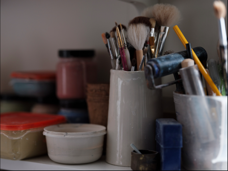 A variety of art materials, brushes and containers.