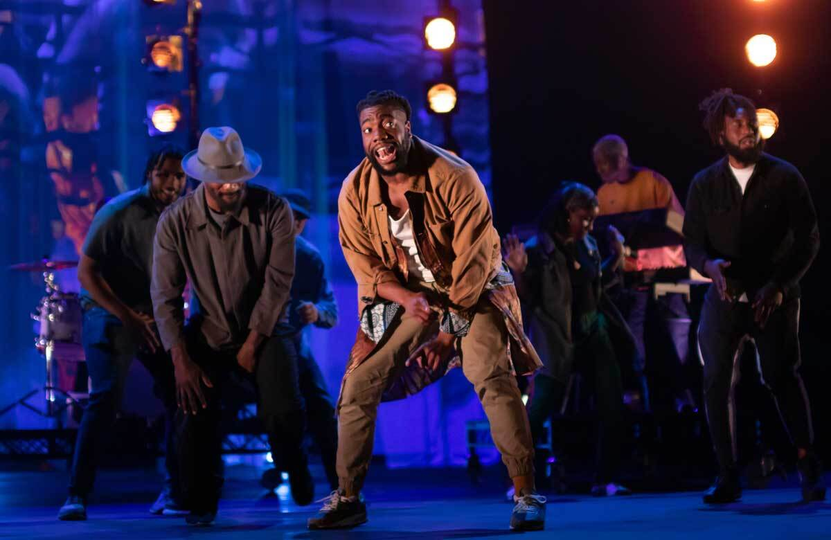 A performer stands on stage for a hip-hop and spoken word performance