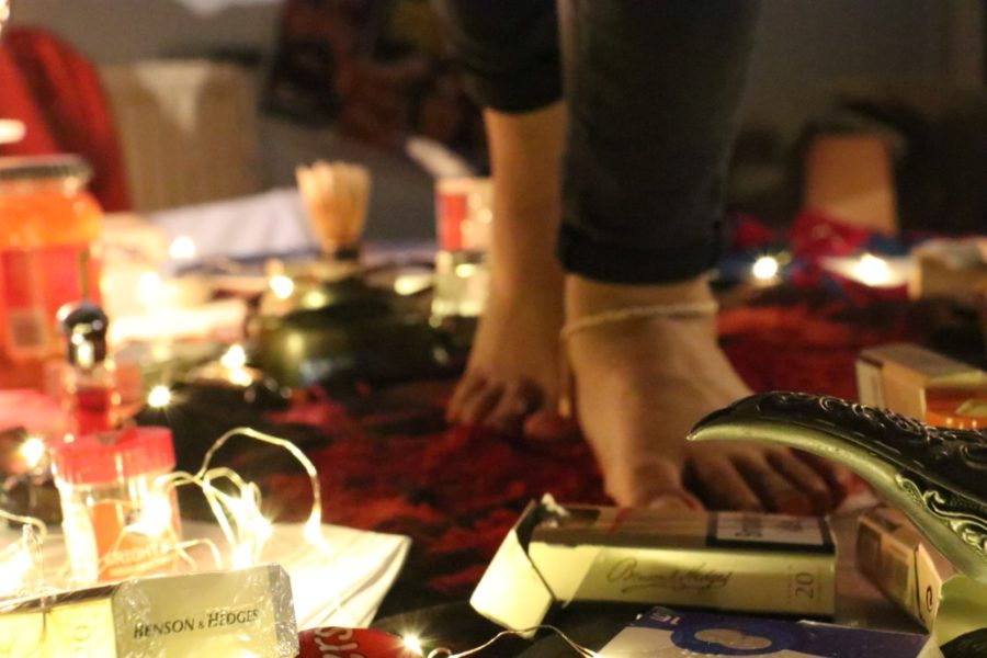 A pair of feet walk on top of a table among fairy lights and packets of cigarettes.