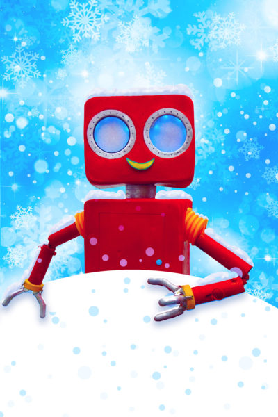 A red robot stands in the snow set against a blue sky.