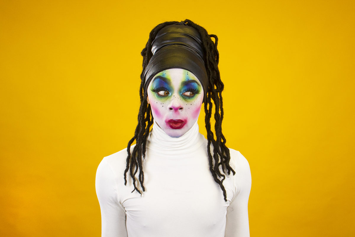 A performer at Vogue Ball stands against a yellow background.