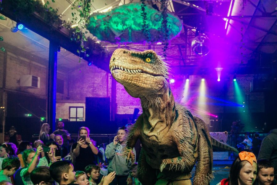 A life-size model of a T-Rex stands in front of a live audience.