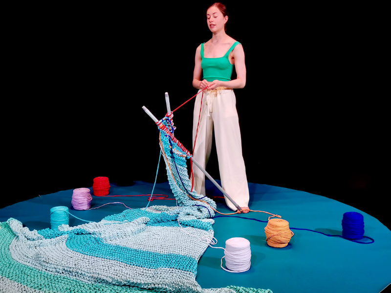 Performer Sophie Ablett stands on a stage with a huge piece of knitting, and brightly coloured balls of wool.