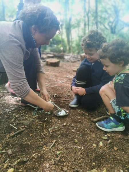 An adult and two small children craft in the woods.