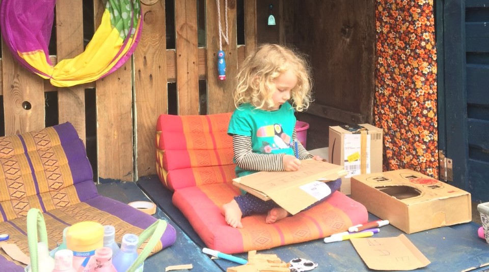 A small child sits crafting inside a den.