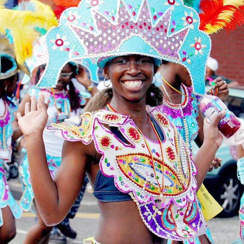 A dancer smiling in a carnival parade.
