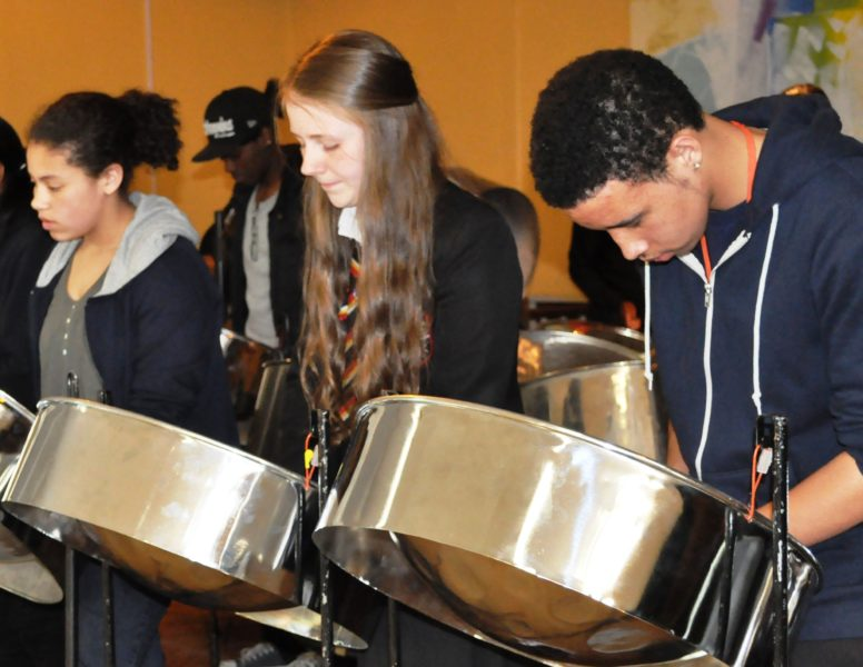 A group of young people playing the steelpans together.