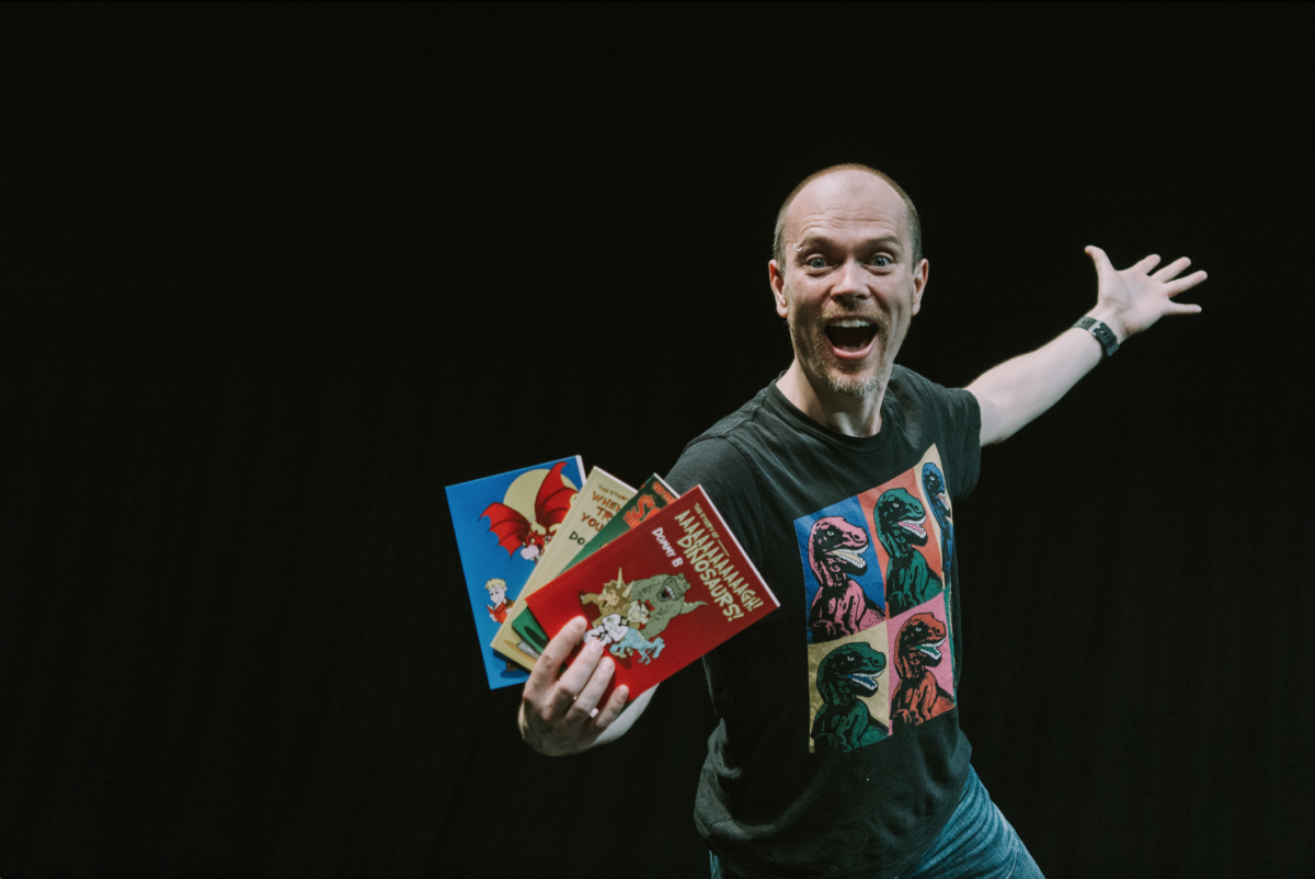 Poet Dominic Berry stands holding three books.