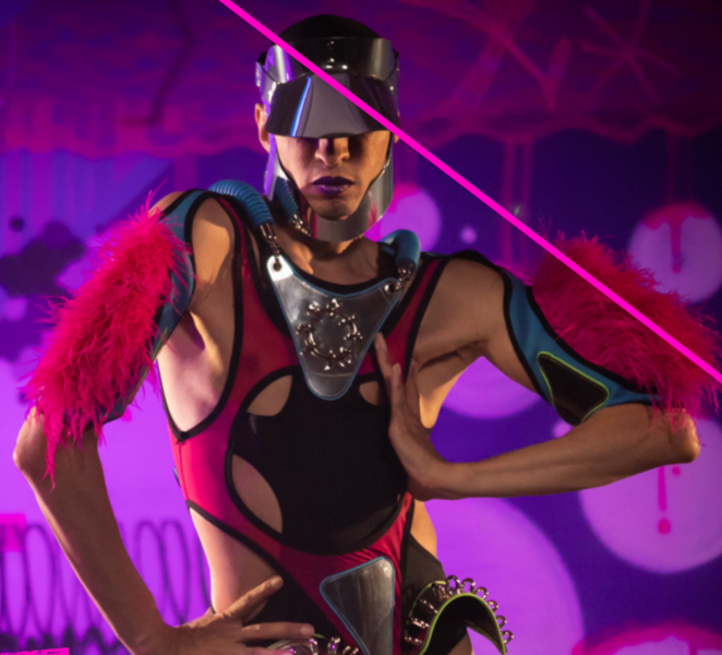 A Vogue dancer poses with their hands on their hips in front of a purple background.