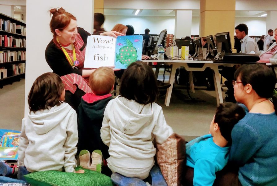 Children sat on the florr being read to and shown a book