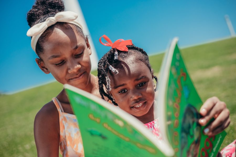 An adult and a child read a book outside together.