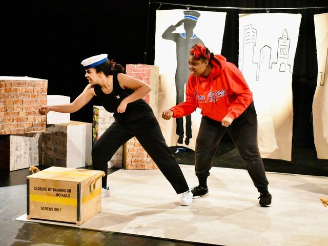 Two actors perform on a stage. One wears a red hoody and the other a captain's sailor hat.