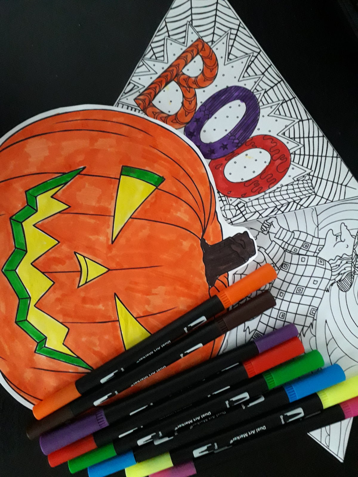 A pumpkin picture, a colouring-in sheet and some coloured felt-tip pens.