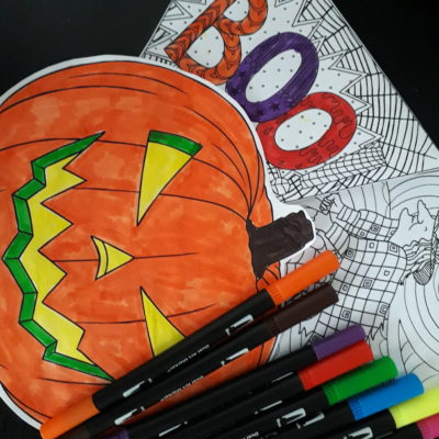 A brightly coloured picture of a pumpkin, a colouring in activity sheet and some felt tip pens.