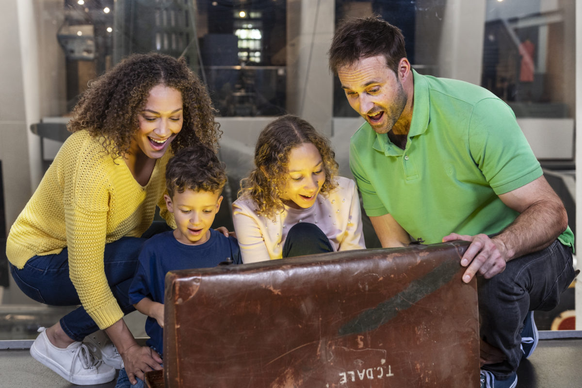 A family of four open an old looking brown leather chest and a light shines out of it. They look excited and happy.