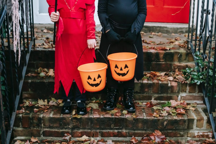 Two children, dressed up for Halloween, stand holding trick or treat buckets.