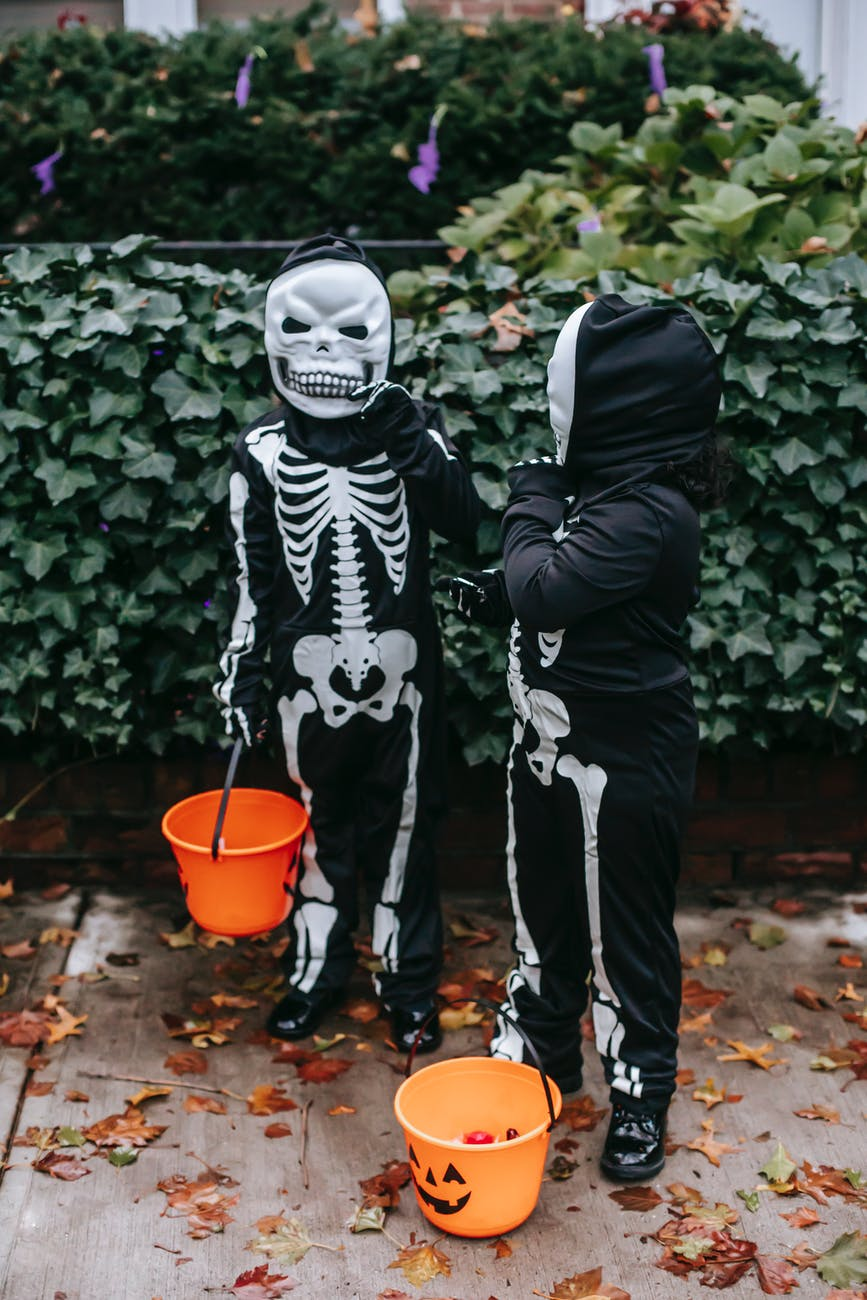 Two children, dressed up as skeletons, carry pumpkin trick or treat buckets.