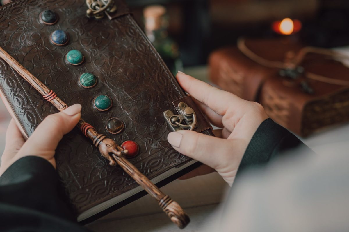 A person holds a spell book and a magic wand