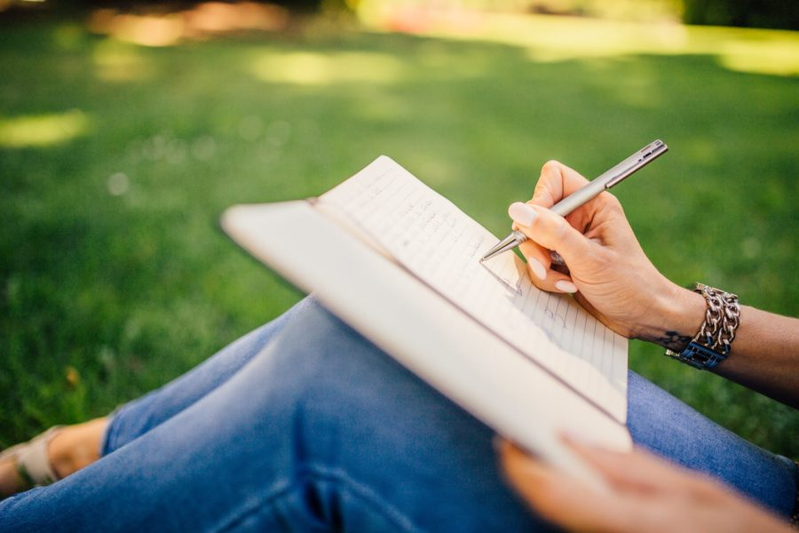 A person sits outside on the grass and writes in a note book.