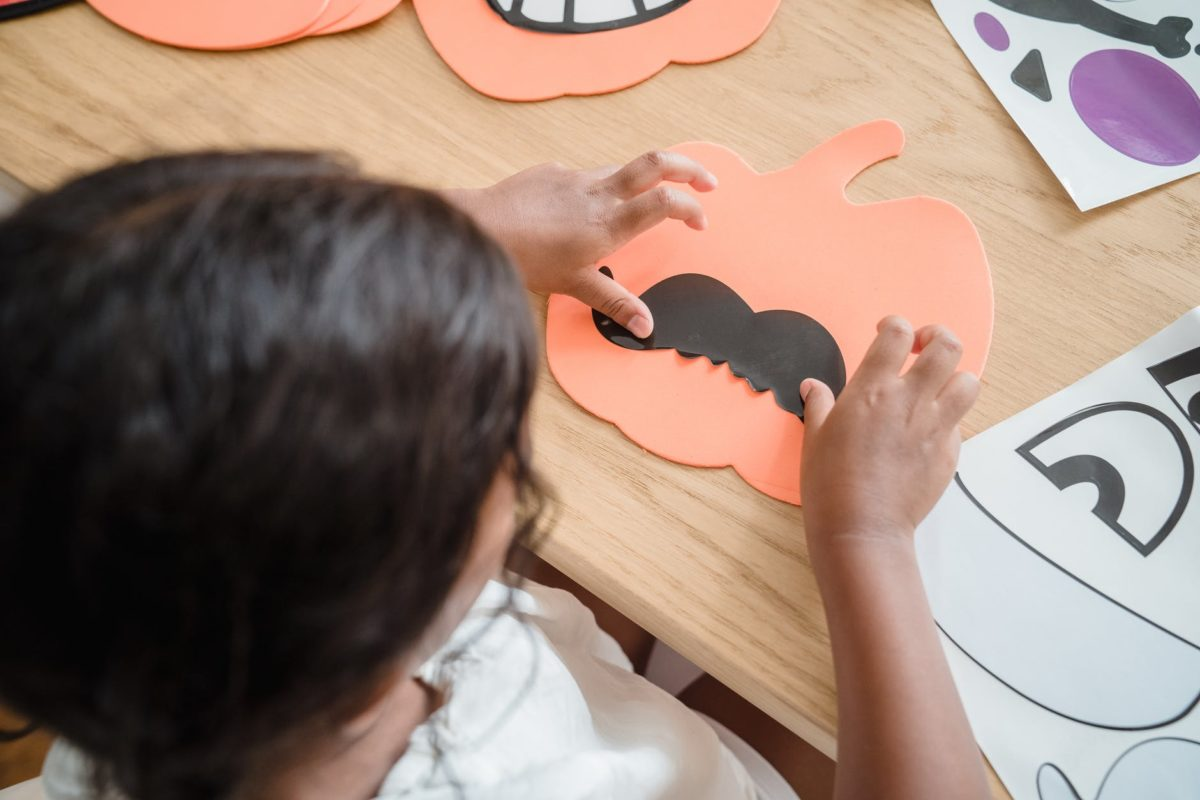 A small child sits at a table doing Halloween craft activities.